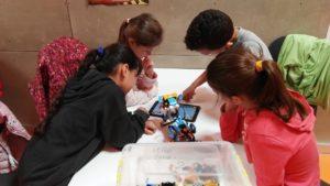 Alumnados enseñando cómo se programa un robot